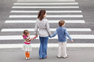 mother holds hands with kids - iStock