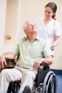 Nurse Pushing Man In Wheelchair - iStock